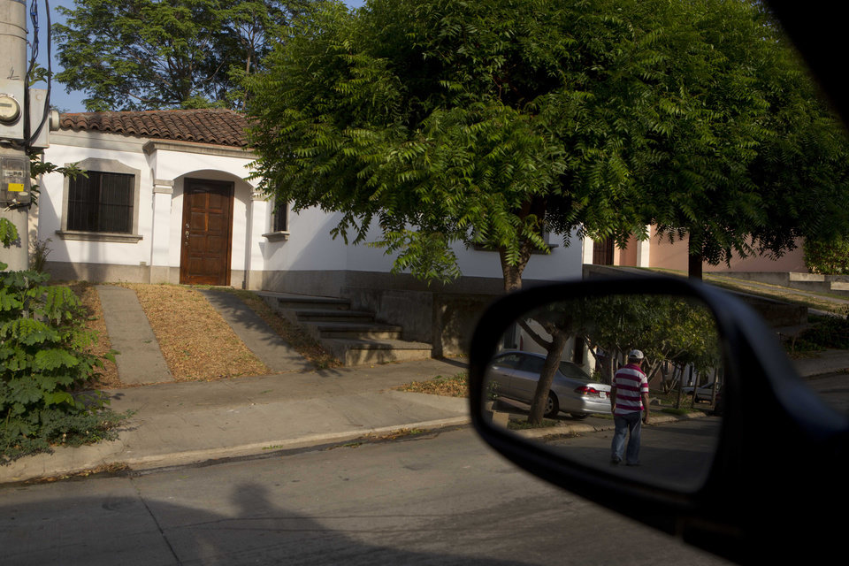 Photo - In this Wednesday, May 7, 2014 photo, a security guard is reflected in a car mirror in front of the house where U.S. citizen William James Vahey lived, near the American Nicaraguan School in Managua, Nicaragua where he worked as teacher from 2013-2014. Vahey, 64, killed himself on March 21, 2014 - two days after agents in Houston filed for a warrant to search a computer thumb drive that belonged to him. The storage device contained pornographic images of at least 90 boys, ages 12 to 14, who appeared to be drugged and unconscious, according to the FBI. (AP Photo/Esteban Felix)