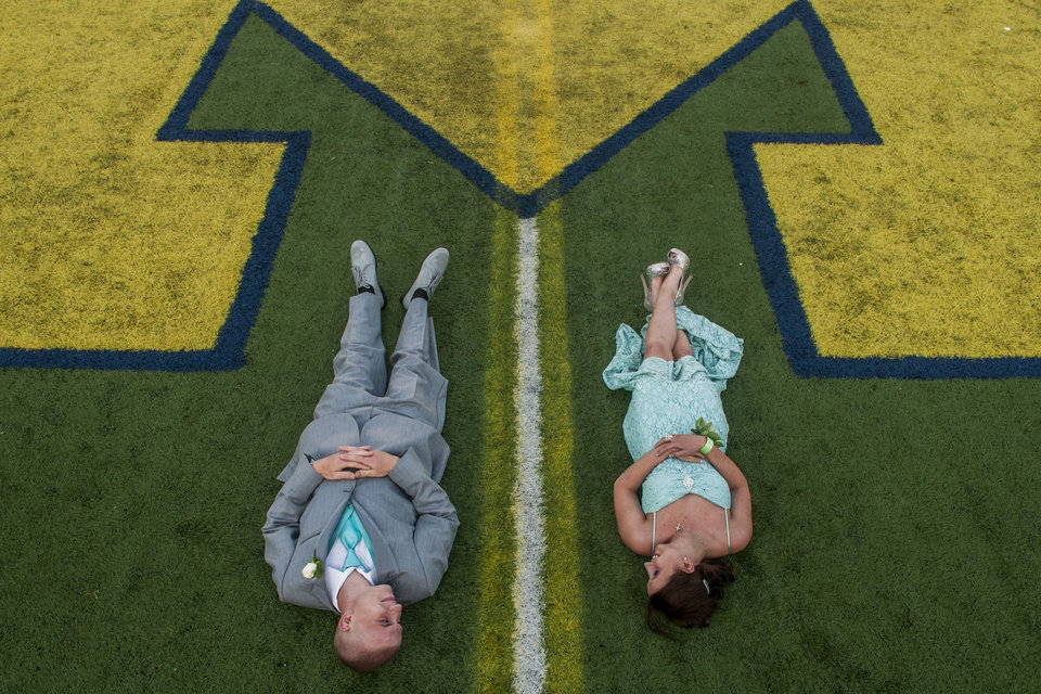 Photo - Durand High School senior David Bedell, 18, left, looks at his girlfriend, sophomore Chelsea Lorenz, 15, as the lay at the 50-yard-line at Michigan Stadium on the University of Michigan campus, Saturday, May 10, 2014, in Ann Arbor, Mich. The junior-senior prom for students at Durand High School was the first prom hosted by the 100,000-plus-seat football venue. The group took photos on the field, visited the locker rooms and had their dancing and dinner in the Jack Roth Stadium Club until midnight. (AP Photo/The Flint Journal, Jake May) LOCAL TV OUT; LOCAL INTERNET OUT