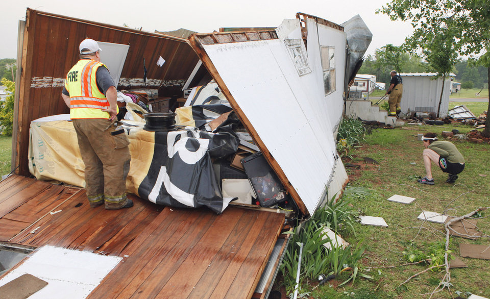 Firemen help Meshelle Reed look for her missing dog, Lexi, after a storm damaged her home Monday in the Prairie Creek Village mobile home park in Noble.  Photo by Steve Sisney, The Oklahoman