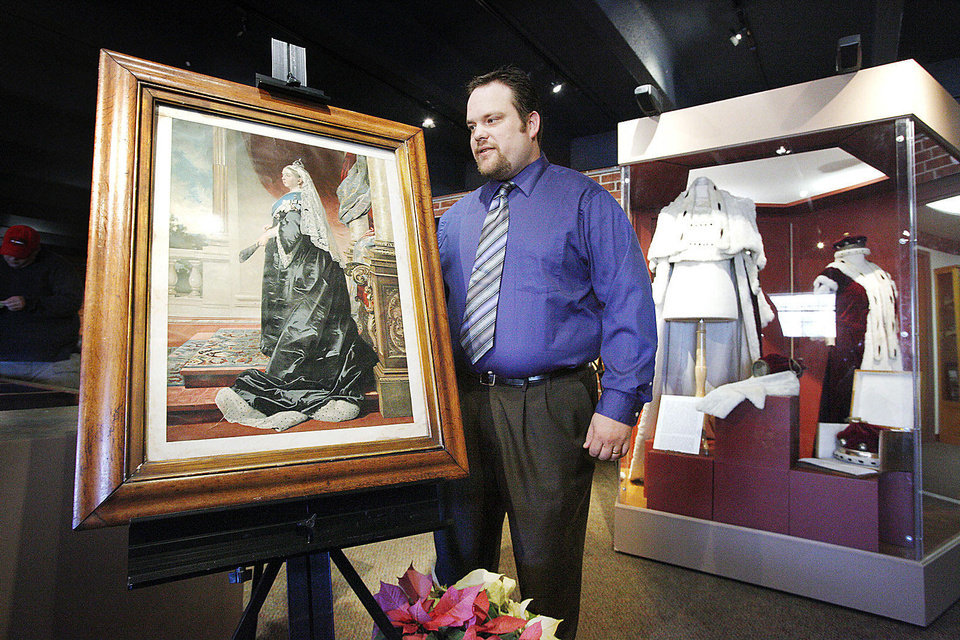 Museum director and curator Adam Lynn standing between a print from the 1800\'s of Queen Victoria and a display case with ceremonial robes belonging to the Burns family of Scotland on display at the Chisholm Trial Museum in Kingfisher Monday, Dec. 17, 2012. The museum has a new exhibit title Queen Victoria and the Victorian Era on display. Photo by Paul B. Southerland, The Oklahoman