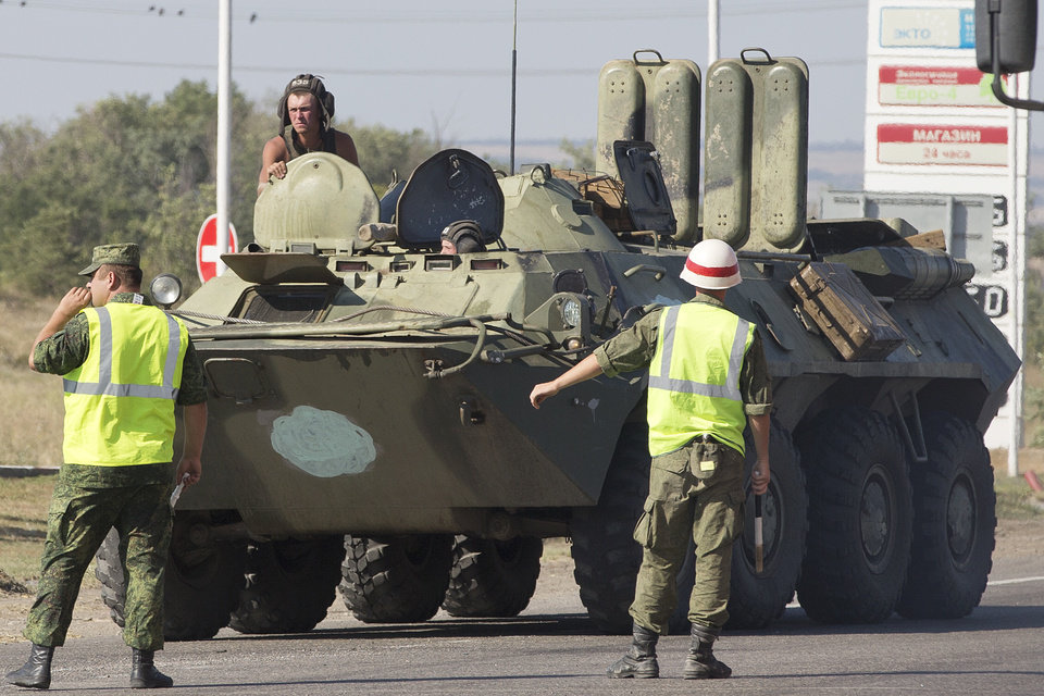 Photo - Military road police direct one of several military vehicles of Russian peacekeeping forces to turn to customs control zone about 28 kilometers from Ukrainian border, Rostov-on-Don region, Russia, Friday, Aug. 15, 2014. Russia let Ukrainian officials inspect an aid convoy on Friday and agreed to allow the Red Cross to distribute the aid around the rebel-held city of Luhansk, easing tensions and dispelling Ukrainian fears that the aid operation is a ruse to get military help to separatist rebels. (AP Photo/Pavel Golovkin)