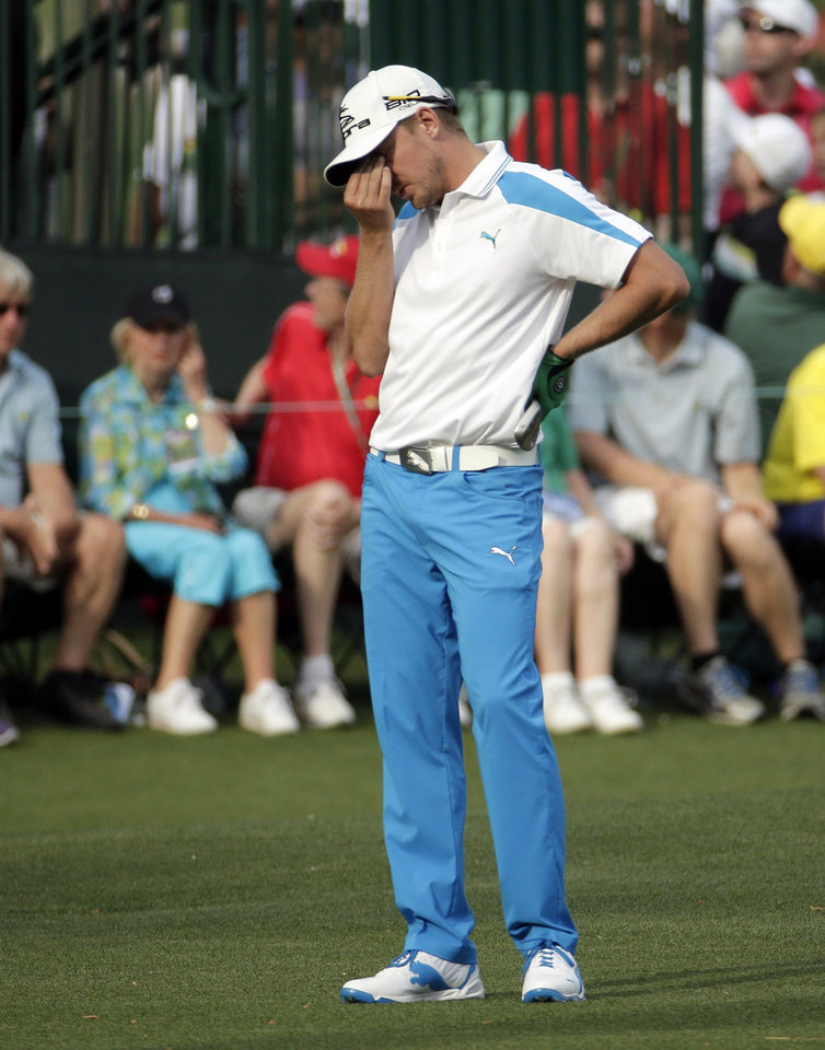 Photo - Jonas Blixt, of Sweden, reacts after his putt on the 15th green during the fourth round of the Masters golf tournament Sunday, April 13, 2014, in Augusta, Ga. (AP Photo/Charlie Riedel)