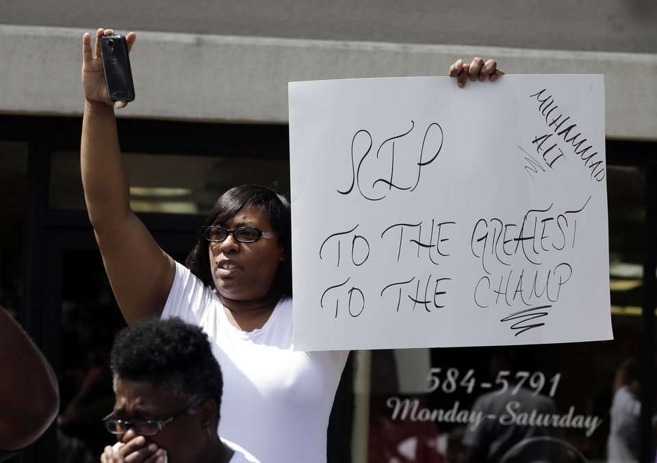 Photo - A mourner holds a sign as the funeral procession for Muhammad Ali makes its way down Muhammad Ali Boulevard in Louisville, Ky. Friday, June 10, 2016. (AP Photo/Michael Conroy)