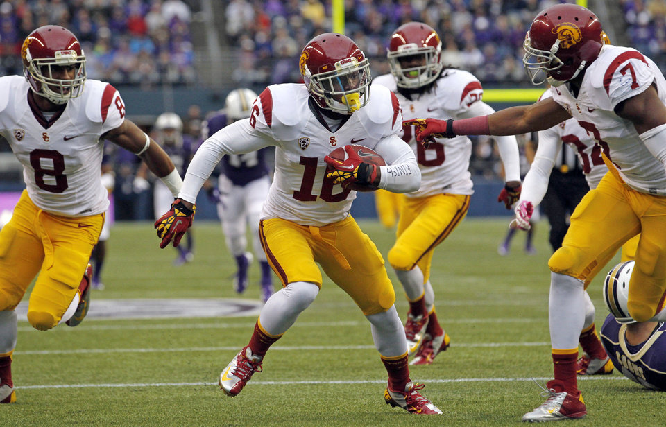 "Photo - FILE - In this Oct. 13, 2013 file photo, Southern California's Anthony Brown, center, runs the ball in for a touchdown after blocking a punt by Washington's Travis Coons during the first half of an NCAA college football game in Seattle. Brown has quit Southern California's football team, and coach Steve Sarkisian was stunned by Brown's apparent accusations of racism against him on social media. ""Couldn't play for a racist man!"" was posted Thursday, Aug. 28, 2014 on what USC said was Brown's Instagram account, which was later deleted. Sarkisian calls the apparent accusation ""ridiculous."" Several players immediately jumped on social media to defend the first-year USC coach. (AP Photo/Elaine Thompson, File)"