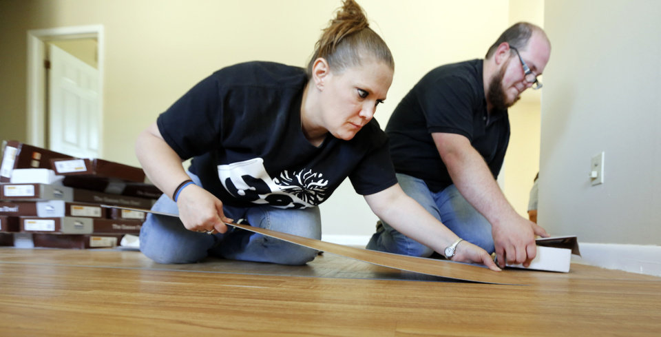 Photo - Karen Smith and Daniel Lacey install new flooring in the living room  of Iraq War veteran Josh Lozier's home in Midwest City. Volunteers from Home Depot were refurbishing Lozier's house. Photo By Steve Gooch, The Oklahoman  Steve Gooch - The Oklahoman