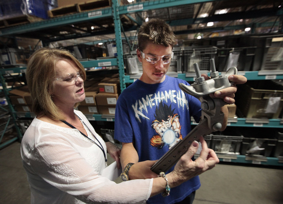 Technical services manager Lorrie Acord shows Bill Factor, an eighth-grade student from Cimarron Middle School, how a span wire hanger works during a tour of Pelco Products Inc. in Edmond Friday. <strong>David McDaniel - The Oklahoman</strong>