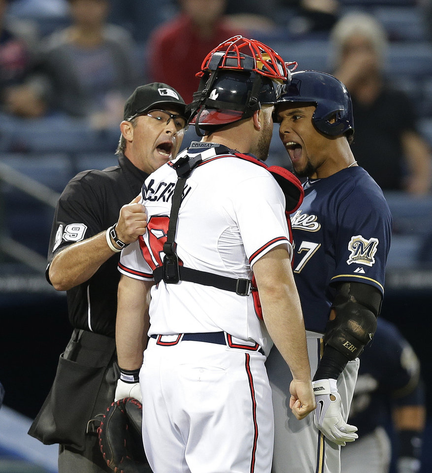 Photo - Milwaukee Brewers' Carlos Gomez (27) and Atlanta Braves catcher Brian McCann (16) are separated by home plate umpire Paul Nauert as they exchange words following a home run by Gomez in the first inning of a baseball game Wednesday, Sept. 25, 2013 in Atlanta. (AP Photo/John Bazemore)