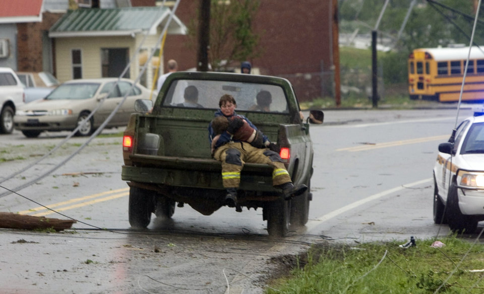 Photo - A first responder holds onto a child that was found in the rubble of a destroyed home after a tornado struck Phil Campbell, Ala. Wednesday afternoon, April 27, 2011. A wave of severe storms laced with tornadoes strafed the South on Wednesday, killing at least 16 people around the region and splintering buildings across swaths of an Alabama university town. (AP Photo/The TimesDaily, Daniel Giles)