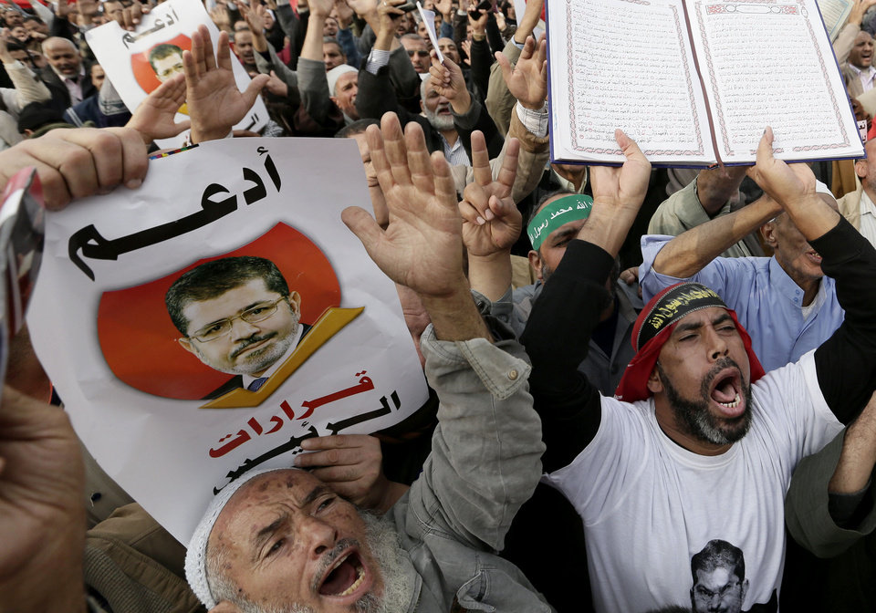 "Supporters of Egyptian President Mohammed Morsi chant slogans as one holds up the Quran, Islam's hold book, during a demonstration after the Friday prayer, in Cairo, Egypt, Friday, Dec. 14, 2012. Opposing sides in Egypt's political crisis were staging rival rallies on Friday, the final day before voting starts on a contentious draft constitution that has plunged the country into turmoil and deeply divided the nation. Arabic on the poster, left, reads, ""support the president's decisions.""   (AP Photo/Hassan Ammar)"