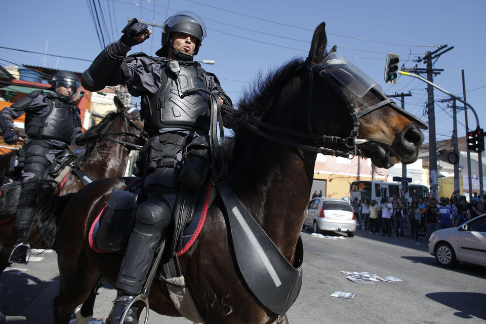Photo - Brazilian riot policeman on horseback advance towards protesters after clashes erupted during a demonstration demanding better public services and against the World Cup costs in Sao Paulo, Brazil, Thursday, June 12, 2014. Police clashed with anti-World-Cup protesters who were trying to block a road near the main highway leading to the stadium that hosts the opening match to the tournament. (AP Photo/Dario Lopez-Mills)