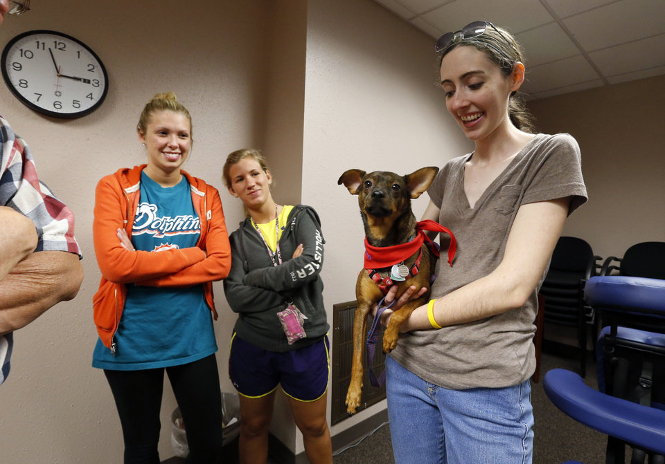 Photo - Elizabeth Maupin holds her therapy dog, Zeus, as University of Oklahoma students Stephanie Allen, left, and Brandi Brooks wait to pet him while on a break from studying for finals. PHOTO BY STEVE SISNEY, THE OKLAHOMAN  STEVE SISNEY