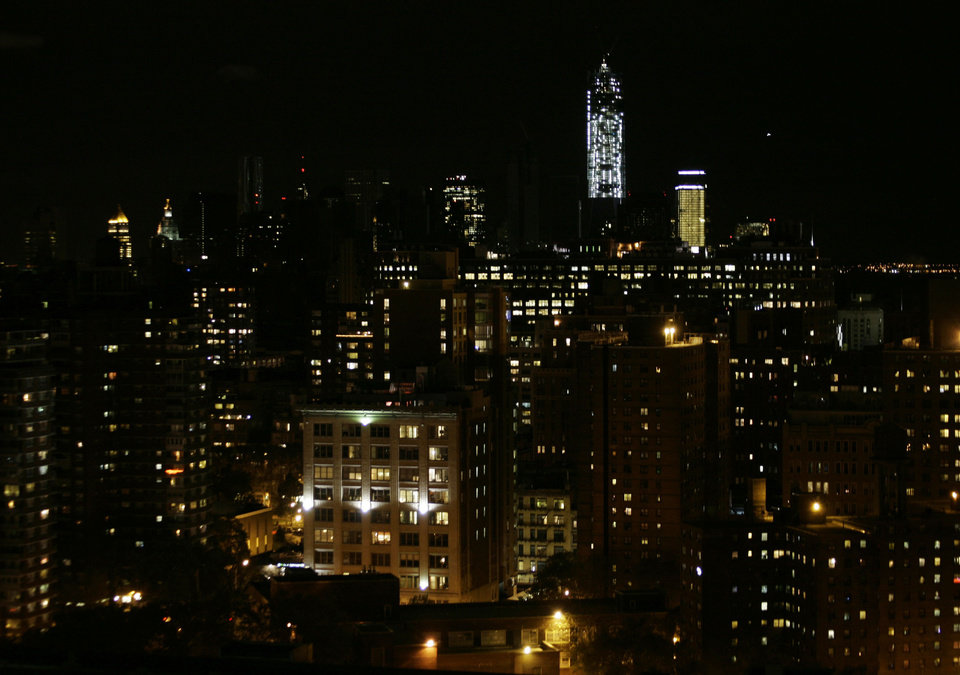 In this photo looking south from 33rd Street in New York City, lights are on in some buildings in Lower Manhattan as power gradually returns to parts of the city darkened by Superstorm Sandy, Friday, Nov. 2, 2012. Con Edison says the lights went back on at around 5 p.m. Friday in apartment buildings and businesses on the Lower East Side and in the East Village. Over the next few hours, power returned to other neighborhoods, from Chelsea, to Union Square, to City Hall. In the center is 1 World Trade Center which never went dark because it has its own power source. (AP Photo/Peter Morgan) ORG XMIT: NYR110