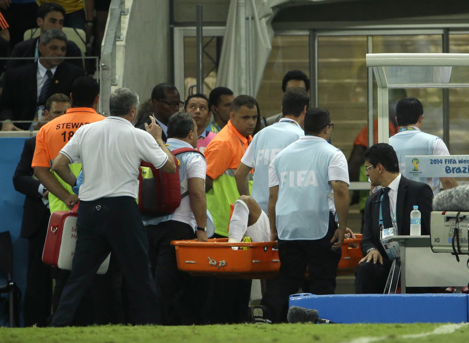 Photo - Brazil's Neymar is taken away on a stretcher after being injured during the World Cup quarterfinal soccer match between Brazil and Colombia at the Arena Castelao in Fortaleza, Brazil, Friday, July 4, 2014. (AP Photo/Hassan Ammar)