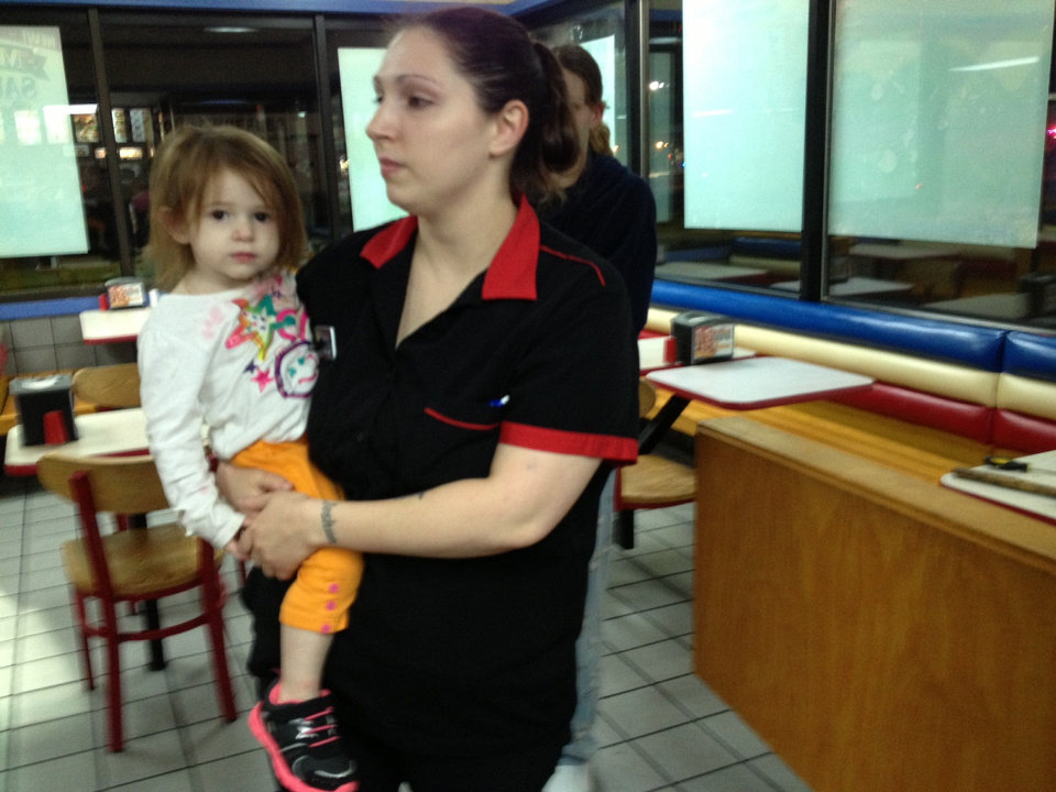 Photo - A van slammed into two unoccupied, parked cars in the parking lot of Carl's Jr. Tuesday night at NW 23 and N MacArthur Blvd. Two employee vehicles burst into flames in the parking lot. A woman fleeing police jumped out of the van and fled on foot. She was arrested nearby. Carl's Jr. Shift supervisor Jessica Graham holds her child. The family's Chevy Tahoe was destroyed.  THE OKLAHOMAN - BY JULIANA KEEPING