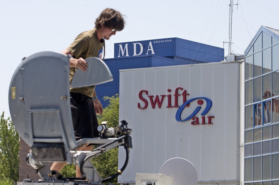 Photo - A television camera operator mounts a satellite dish on top of a van outside the Swiftair offices in Madrid,  Spain, Thursday, July 24, 2014.  A flight operated by Air Algerie and carrying 116 people from Burkina Faso to Algeria's capital disappeared from radar early Thursday, the plane's operator said. Swiftair, a private Spanish airline, said the plane carrying over 100 passengers and crew left Burkina Faso for Algiers at 0117 GMT Thursday (9:17 p.m. EDT Wednesday), but had not arrived at the scheduled time of 0510 GMT (1:10 a.m. EDT Thursday). (AP Photo/Paul White)
