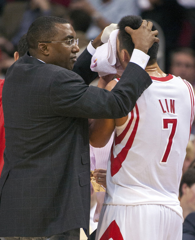 Houston Rockets trainer Keith Jones, left, helps Jeremy Lin (7) control a bloody nose after he was fouled during the fourth quarter of an NBA basketball game against the Golden State Warriors, Tuesday, Feb. 5, 2013, in Houston. The Rockets beat the Warriors 140-109. (AP Photo/Dave Einsel)