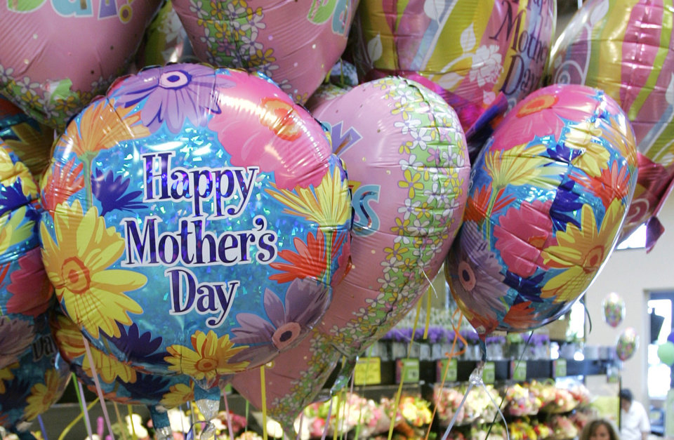 Photo - A shopper walks through the floral displays at a Kroger supermarket, Monday, May 5, 2008, in Cincinnati. Moms may not be getting quite as much this year for Mother's Day as consumers feeling the economic pinch watch their spending. Even businesses that traditionally benefit from the holiday are reaching out with special offers and products. (AP Photo/Al Behrman) ORG XMIT: OHAB502