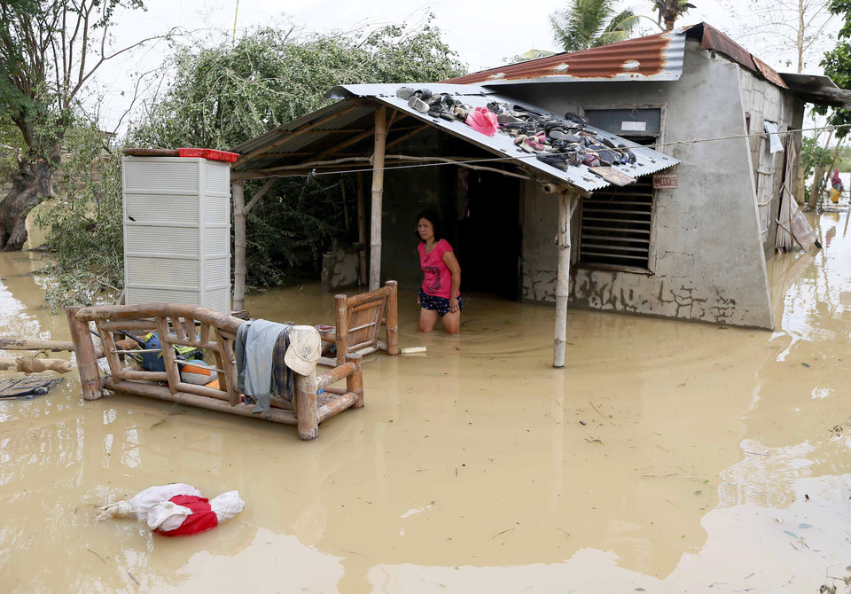 Photo - A resident wades through her flooded home in Cabanatuan, northern Philippines, Tuesday, Oct. 20, 2015, two days after Typhoon Koppu battered the city and nearby provinces. Slow-moving Typhoon Koppu blew ashore with fierce wind in the northeastern Philippines early Sunday, toppling trees and knocking out power and communications and forcing the evacuation of thousands of villagers. (AP Photo/Bullit Marquez)