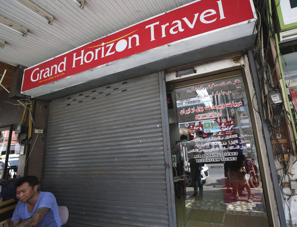 Photo - A man sits in front of closed door of the Grand Horizon Travel office in Pattaya, Chonburi province, Thailand, Monday, March 10, 2014. Thai police said owners of the travel agency told them they had received orders from a China Southern Airlines office in Bangkok for Malaysia Airlines flight MH370 for two individuals who boarded the flight with fake passports. (AP Photo/Sakchai Lalit)