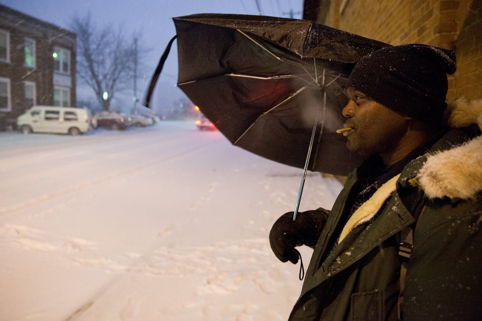 Photo - Charles Crisp stands across the street from My Brother's Keeper emergency men's shelter smoking a cigarette before seeking refuge from the snow and cold on Wednesday, Dec. 26, 2012 in Flint, Mich. Snow began falling around 3pm in Genesee County and a winter weather advisory is in effect until 7am Thursday. Up to four inches of snowfall is expected in the area. (AP Photo/The Flint Journal, Griffin Moores) LOCAL TV OUT; LOCAL INTERNET OUT