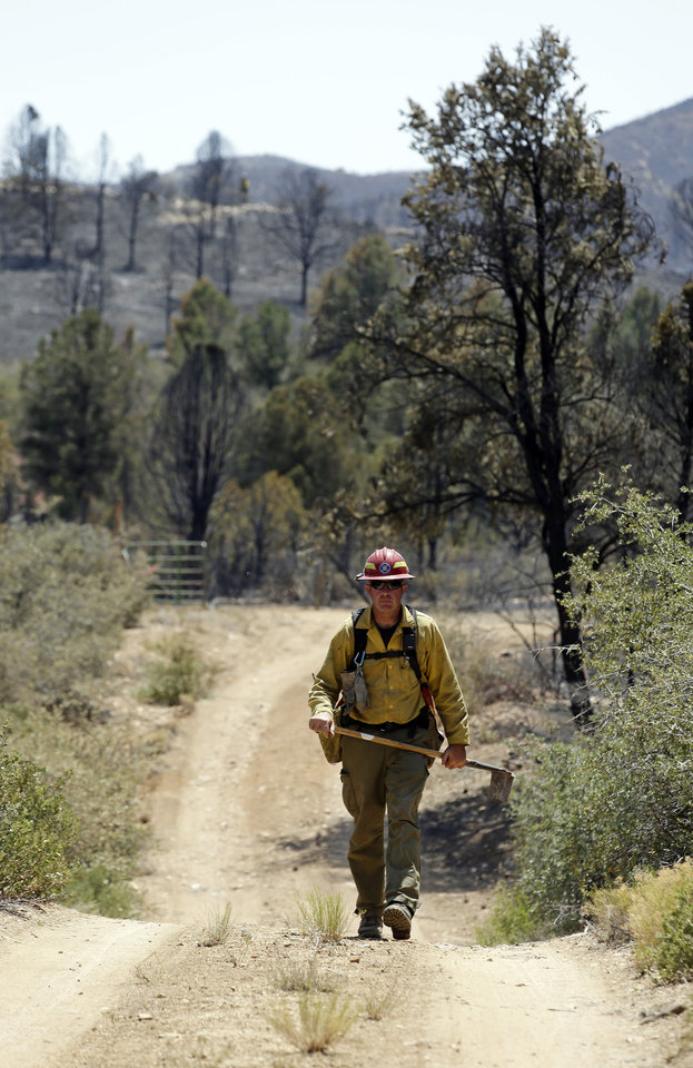 Photo - A firefighter walks along a dirt path while battling a wildfire near Yarnell, Ariz., Wednesday, July 3, 2013. More than 100 homes and structures have been burned in the wildfire that claimed the lives of 19 members of an elite firefighting crew. (AP Photo/Chris Carlson)