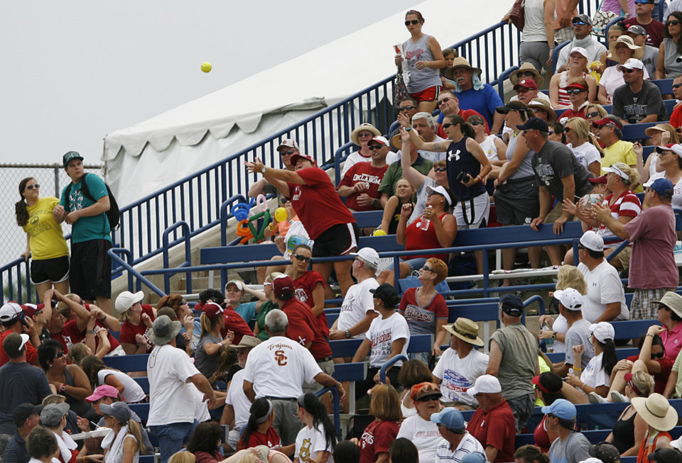Fans try to catch a foul ball during a Women's College World Series game between Oklahoma University and Arizona State University at ASA Hall of Fame Stadium in Oklahoma City, Sunday, June 3, 2012.  Photo by Garett Fisbeck, The Oklahoman