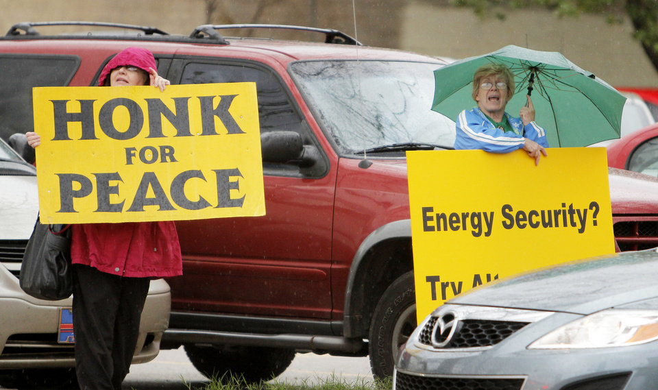 Photo - Fannie Bates, left, and Mary Francis protest Wednesday at Reno Avenue and E.K. Gaylord Boulevard.  Photos by Doug Hoke, The Oklahoman