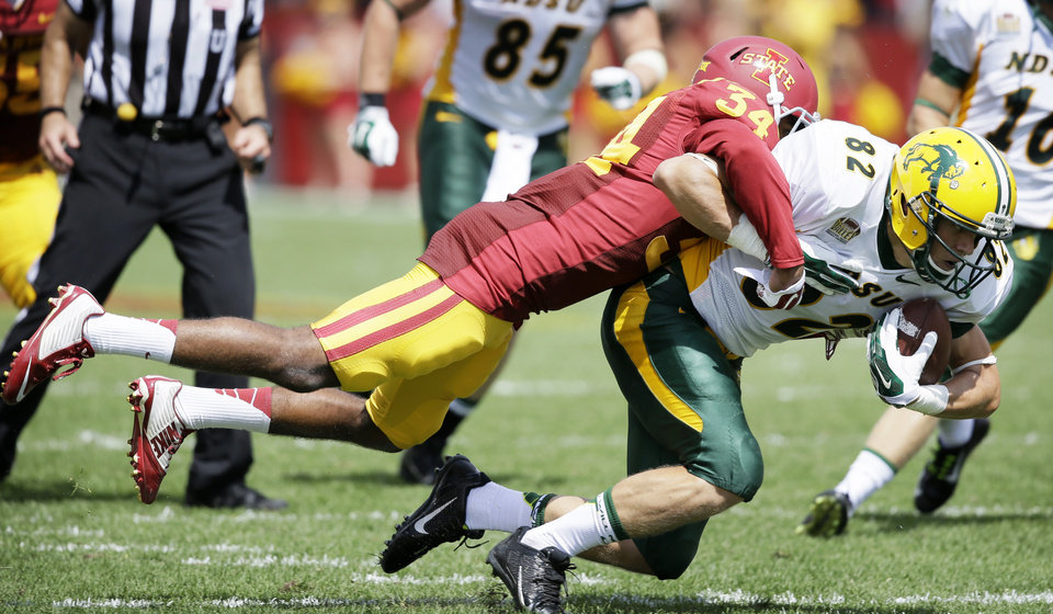 Photo - North Dakota State wide receiver Zach Vraa (82) tries to break a tackle by Iowa State defensive back Nigel Tribune (34) after making a reception during the second half of an NCAA college football game, Saturday, Aug. 30, 2014, in Ames, Iowa. North Dakota State won 34-14. (AP Photo/Charlie Neibergall)