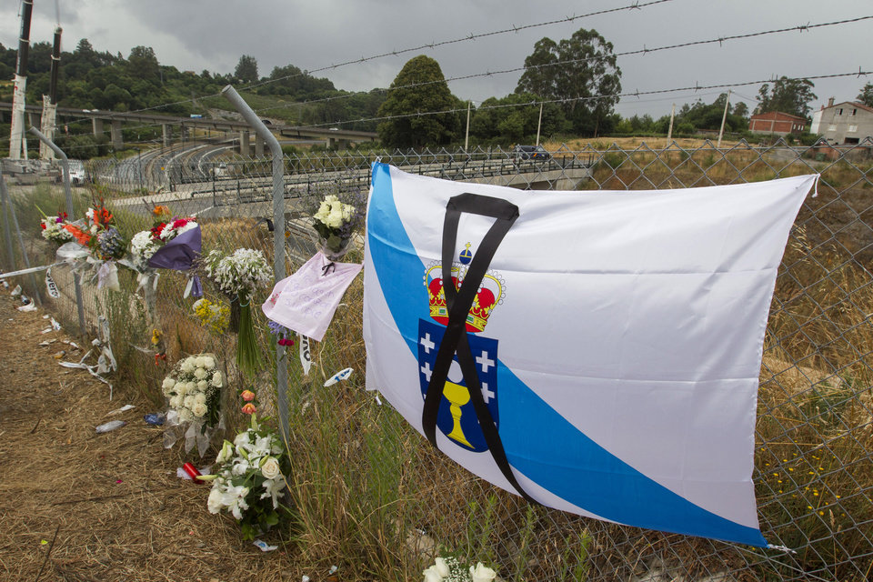 Photo - Bouquets and a Galician type flag with a black ribbon signaling mourning are seen by the train crash site in Santiago de Compostela, Spain, Sunday July 28, 2013. Spain's interior minister Jorge Fernandez Diaz says the driver whose speeding train crashed, killing 78 people, is now being held on suspicion of negligent homicide. The Spanish train derailed at high speed Wednesday killing 78 and injuring dozens more. (AP Photo/Lalo R. Villar)