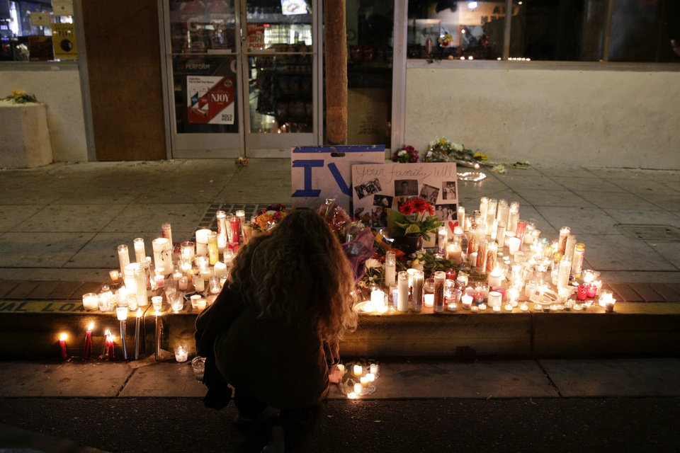 Photo - A woman places a candle in front of IV Deli Mart, where par of Friday night's mass shooting took place by a drive-by shooter, on Saturday, May 24, 2014, in the beach community of Isla Vista, Calif. Sheriff's officials say Elliot Rodger, 22, went on a rampage near the University of California, Santa Barbara, stabbing three people to death at his apartment before shooting and killing three more in a crime spree through a nearby neighborhood. (AP Photo/Jae C. Hong)