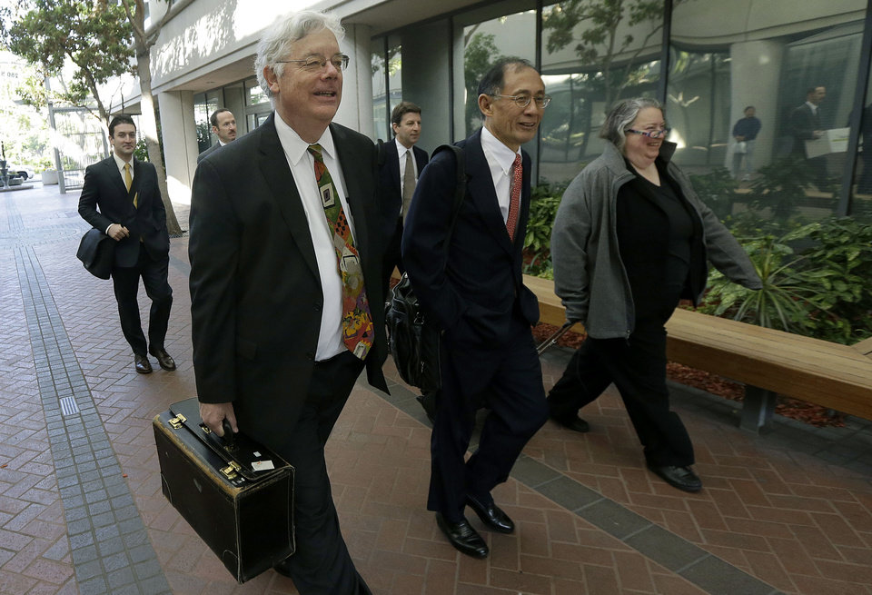 Photo - ADDS ID'S, UPDATES CAPTION INFO - Apple attorneys Harold McElhinny, left, William Lee, center, and Rachel Krevans walk with others to a federal courthouse in San Jose, Calif., Monday, April 28, 2014. A federal court has delayed by a day closing arguments in the Apple and Samsung trial because of an appeals court ruling in another case on a related patent issue. Dueling expert witnesses were called back to the stand Monday in a San Jose federal courtroom to discuss whether the ruling in a legal dispute between Apple and Motorola has any effect on the Apple and Samsung trial. Lawyers will now deliver closing arguments Tuesday. (AP Photo/Jeff Chiu)