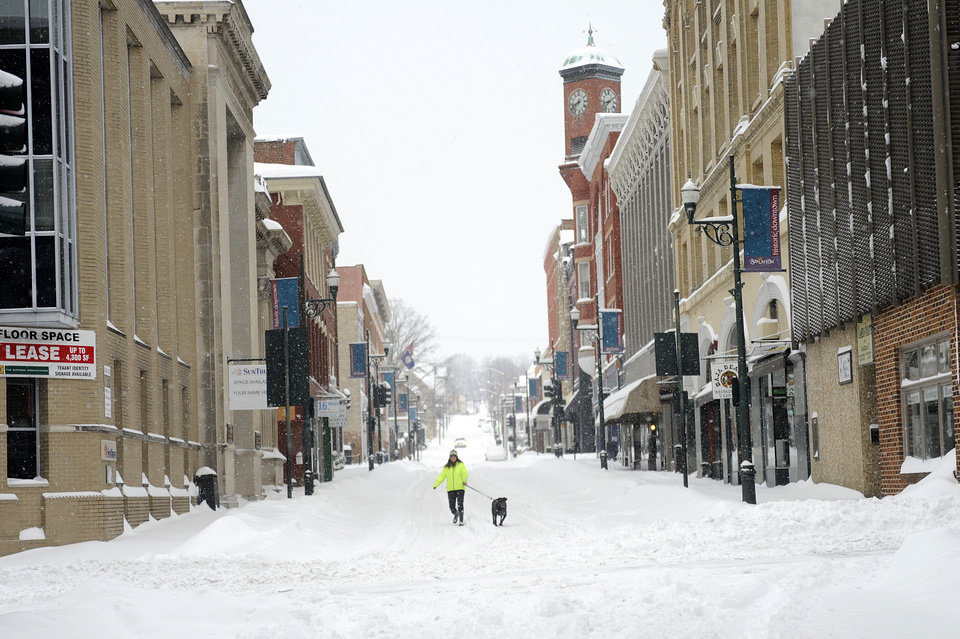 Photo - Gerry Stowers walks her dog, Jane Rambo, down the middle of Beverley Street after a snowstorm accumulating over a foot of snow fell on Thursday, Feb. 13, 2014, in Staunton, Va. (AP Photo/The News Leader, Katie Currid)