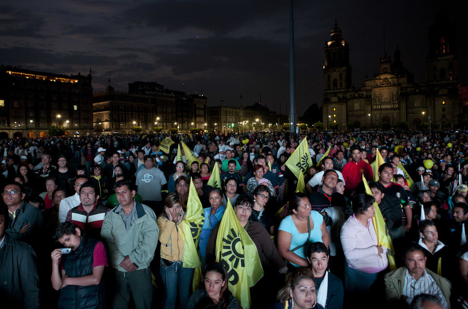 Photo -   People watch the first televised presidential debate at Mexico City's main Zocalo plaza, Sunday, May 6, 2012. Next July 1, Mexico will hold presidential elections. (AP Photo/Eduardo Verdugo)