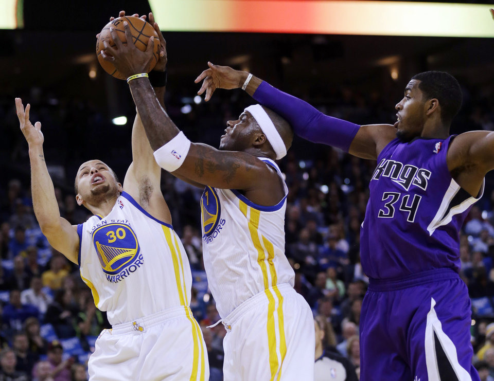 Photo - From left, Golden State Warriors guard Stephen Curry and center Jermaine O'Neal and Sacramento Kings forward Jason Thompson (34) vie for a rebound during the first half of an NBA basketball game Friday, April 4, 2014, in Oakland, Calif. (AP Photo/Marcio Jose Sanchez)