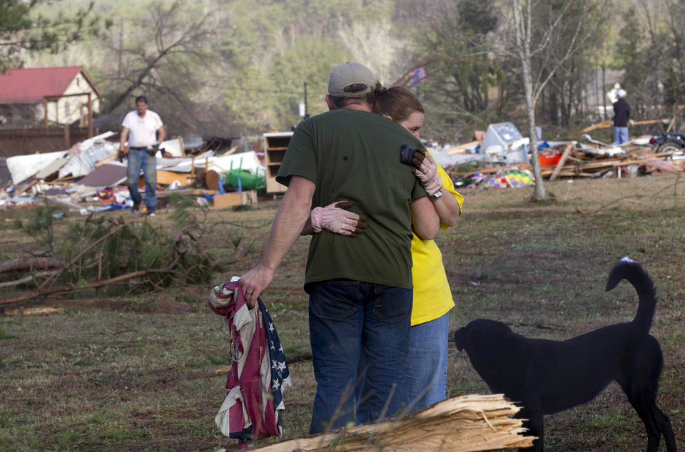 Russ Butler hugs his wife, Amber, as their friends and neighbors begin the cleanup process in Oak Grove, Ala., Monday, Jan. 23, 2012. At least one person was killed when a suspected tornado swept through the area overnight.  (AP Photo/Dave Martin) ORG XMIT: ALDM101