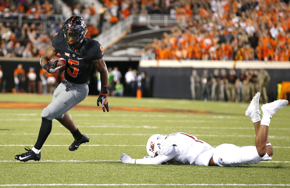 Photo - Oklahoma State's Justice Hill (5) gets by South Alabama's Jalen Thompson (1) on the way to a touchdown in the second quarter  during a college football game between Oklahoma State (OSU) and South Alabama at Boone Pickens Stadium in Stillwater, Okla., Saturday, Sept. 8, 2018. Photo by Sarah Phipps, The Oklahoman