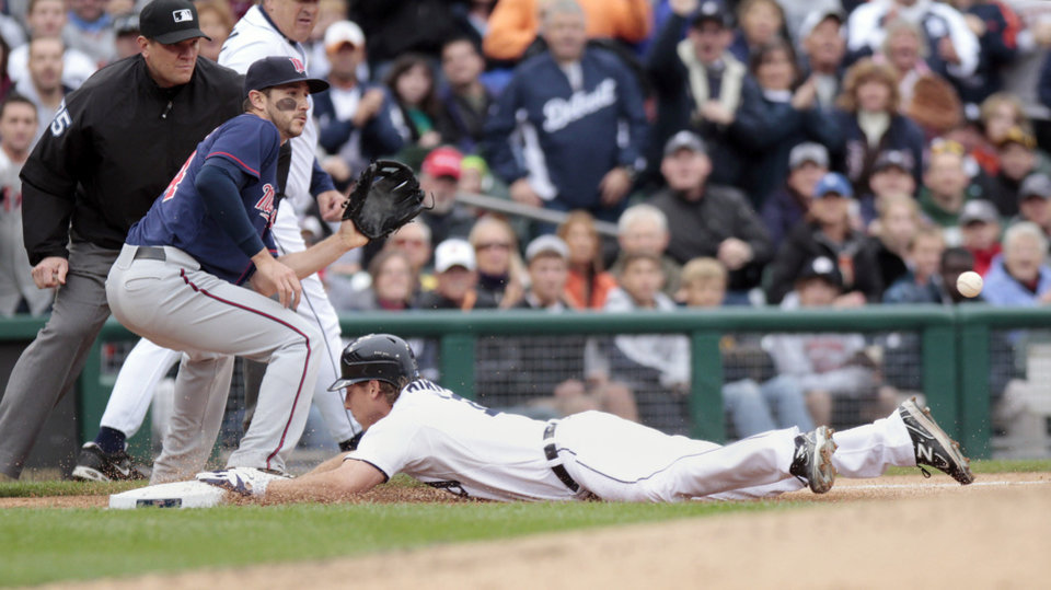Photo -   Detroit Tigers' Andy Dirks, right, dives into third base for a triple, beating the throw to Minnesota Twins third baseman Trevor Plouffe during the third inning of a baseball game Saturday, Sept. 22, 2012, in Detroit. (AP Photo/Duane Burleson)