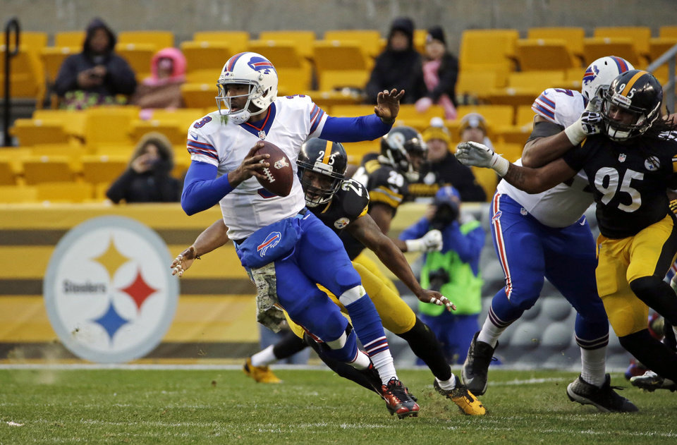 Photo - FILE - In this Nov. 10, 2013, file photo, Buffalo Bills quarterback EJ Manuel, left, is flushed out of the pocket by Pittsburgh Steelers free safety Ryan Clark (25) and Jarvis Jones (95) during an NFL football game in Pittsburgh. As TV ratings stay strong, the number of people showing up for games, even in the places that are traditionally hot tickets, is dwindling. (AP Photo/Gene J. Puskar, File)
