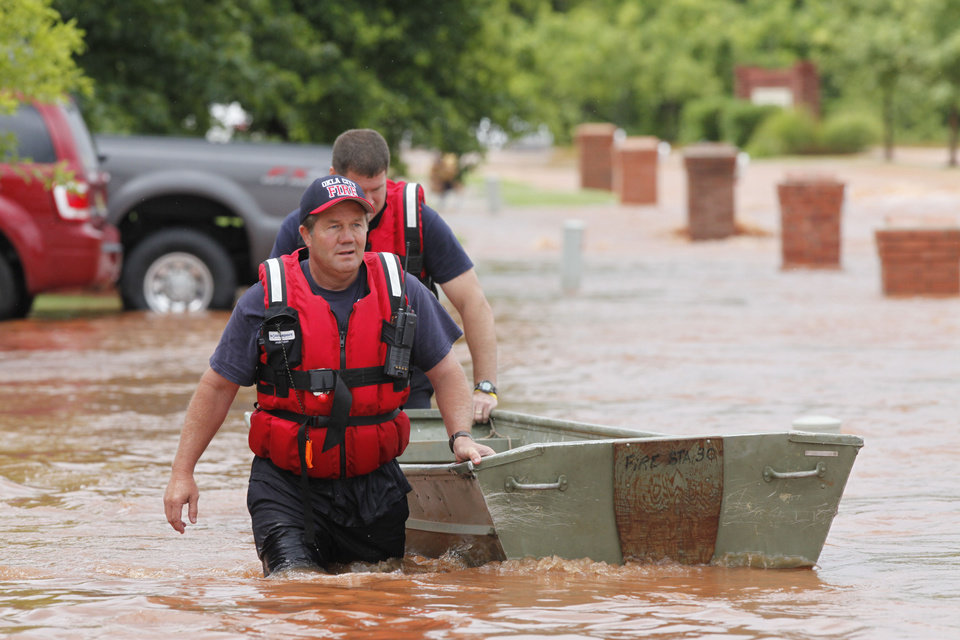 Photo - An Oklahoma City Fire Dept. crew brings a rescue boat into the Palo Verde Addition in Edmond, OK, after flood waters inundated a number of homes in the area, Monday, June 14, 2010. By Paul Hellstern, The Oklahoman