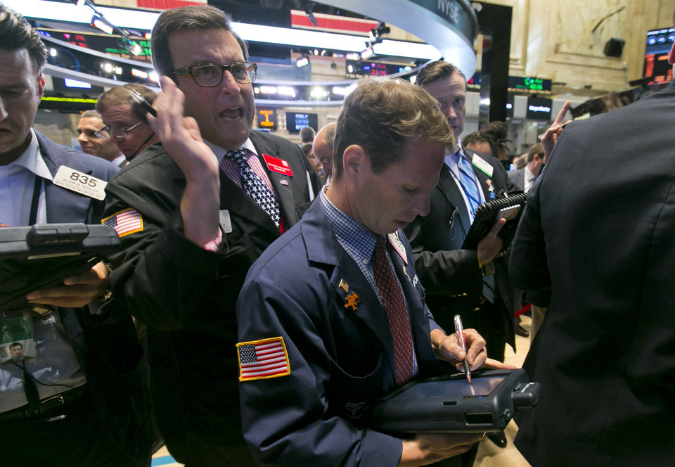 Photo - Trader Benedict Willis, left, calls out as he works on the floor of the New York Stock Exchange Friday, Aug. 1, 2014.  U.S. markets steadied on Friday a day after a major sell-off. Investors focused on a relatively strong jobs report, which showed the U.S. economy created 209,000 jobs in July, the sixth straight month of job growth above 200,000. (AP Photo/Richard Drew)