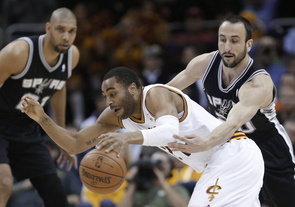 San Antonio Spurs' Manu Ginobili, right, tries to knock the ball loose from Cleveland Cavaliers' Wayne Ellington during the first quarter of an NBA basketball game Wednesday, Feb. 13, 2013, in Cleveland. (AP Photo/Tony Dejak)