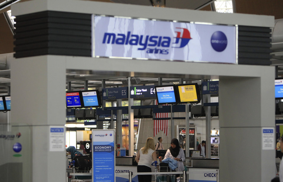 Photo - Passengers are ready to check in at a departure lobby at Kuala Lumpur International Airport in Sepang, Malaysia, Friday, Aug. 29, 2014. Malaysia Airlines will cut 6,000 workers as part of an overhaul announced Friday to revive its damaged brand after being hit by double passenger jet disasters.(AP Photo/Lai Seng Sin)