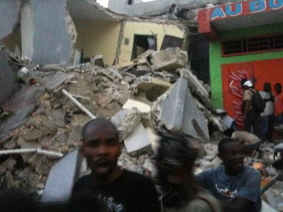 Photo - This photo provided by Carel Pedre shows people running past rubble of a damaged building in Port-au-Prince,  Haiti, Tuesday, Jan. 12, 2010. The largest earthquake ever recorded in the area shook  Haiti on Tuesday, collapsing a hospital where people screamed for help. (AP Photo/Carel Pedre)