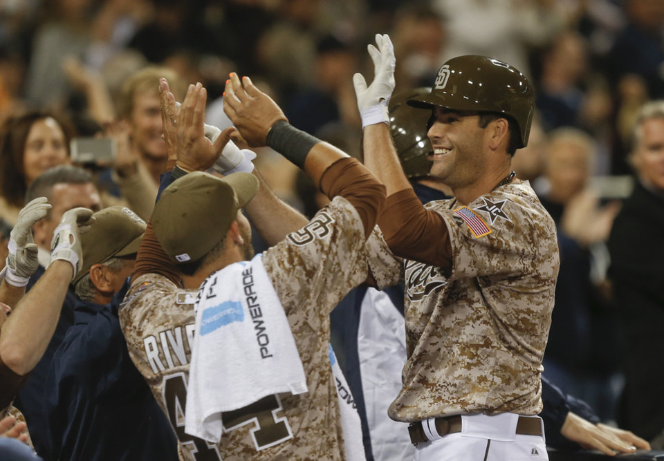 San Diego Padres Seth Smith is greeted at the dugout after his game tieing home run against the Los Angeles Dodgers in the eighth inning of the opening game of Major League baseball in the United States Sunday, March 30, 2014, in San Diego.  (AP Photo/Lenny Ignelzi)