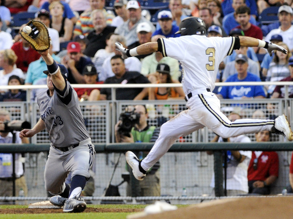 Photo - Vanderbilt's Vince Conde (3) can't beat the throw to first base against UC Irvine first baseman Connor Spencer (33) in the fifth inning of an NCAA baseball College World Series game in Omaha, Neb., Monday, June 16, 2014. (AP Photo/Eric Francis)
