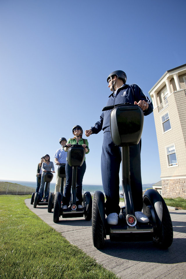 This 2010 photo provided by the Ritz-Carlton Half-Moon Bay shows a hotel recreational staff member leading a group of hotel guests on a Segway tour of the Coastal Trail in Half-Moon Bay, Calif., on the Pacific Ocean with the hotel property on a nearby cliff. A number of hotels offer Segway tours as a novel way to see their grounds and nearby scenic areas. (AP Photo/Ritz-Carlton)