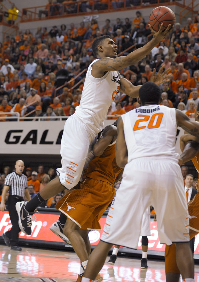 Oklahoma State forward Michael Cobbins, right, watches as Le'Bryan Nash, left, takes a shot while being fouled by Texas guard Julien Lewis during the second half of an NCAA college basketball game in Stillwater, Okla., Saturday, March 2, 2013. Nash scored 16 points Oklahoma State's 78-65 win. (AP Photo/Brody Schmidt)