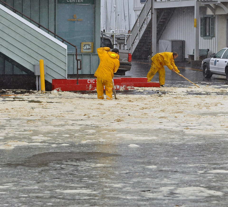 Photo - Workers try to clear drains at the Santa Barbara, Calif., harbor after high waves breached a sand berm and flooded the parking lot Saturday, March 1, 2014. The storm marked a sharp departure from many months of drought that has grown to crisis proportions for the state's vast farming industry. However, such storms would have to become common to make serious inroads against the drought, weather forecasters have said.  (AP Photo/Santa Barbara News-Press, Mike Eliason)