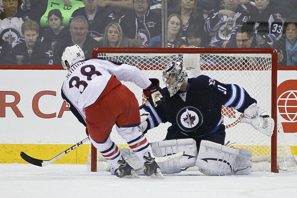 Photo - Columbus Blue Jackets' Boone Jenner (38) scores on the penalty shot against Winnipeg Jets' goaltender Ondrej Pavelec (31) during second period of an NHL hockey game in Winnipeg, Manitoba, on Saturday, Jan. 11, 2014. (AP Photo/The Canadian Press, John Woods)