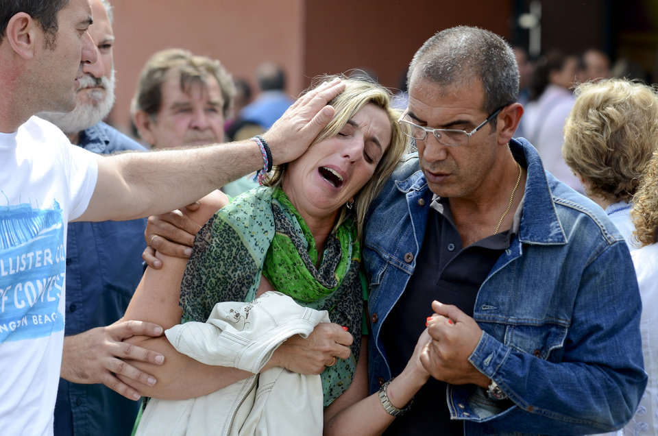 Photo - Relatives of victims involved in a train accident react at a victims information point in Santiago de Compostela, Spain, on Thursday July 25, 2013. Relatives of victims from a train crash in northwestern Spain sobbed and hugged each other Thursday near a makeshift morgue in a sports arena for the victims as the death toll rose to 78 and investigators tried to determine the cause. The train jumped the tracks and at least one passenger told a radio station that it appeared to be going very fast as it went into a pronounced curve while approaching the station in this Catholic shrine city on the eve of a major religious festival. (AP Photo/Brais Lorenzo)